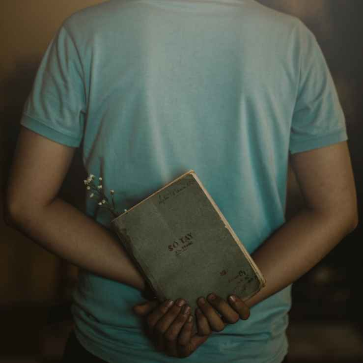 man wearing t shirt holding book